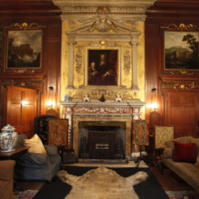 Historic wooden living room with paintings and fire-place
